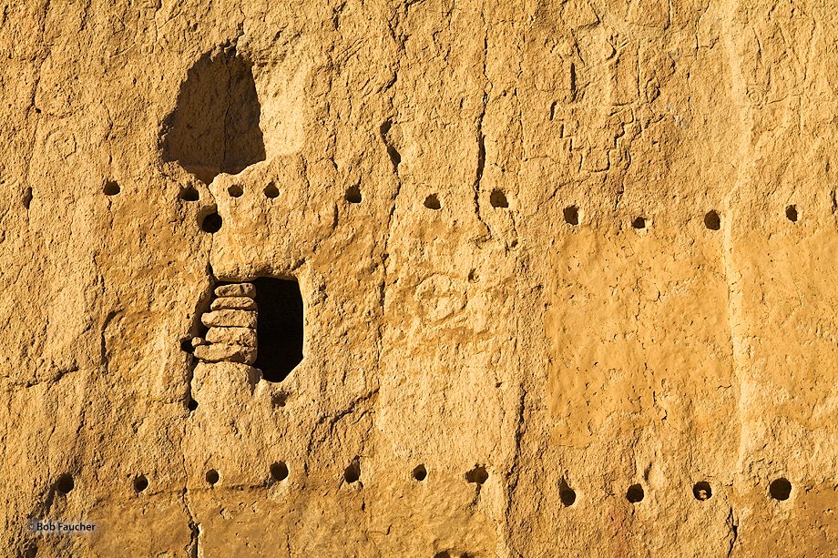 A section of the Long House wall in Bandelier NM featuring petroglyphs, viga holes and storage spaces
