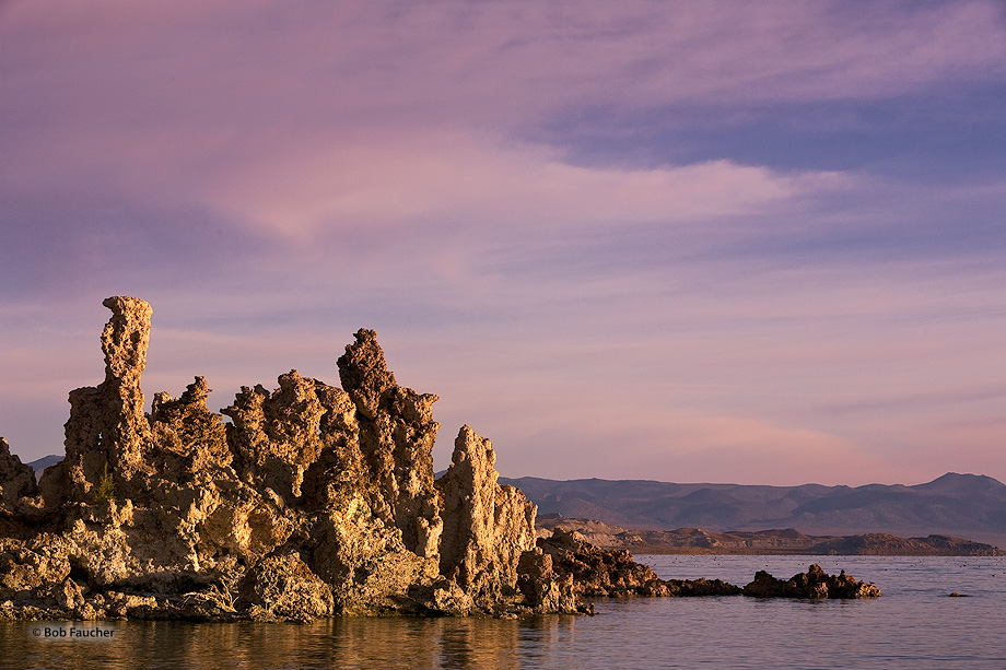A large shoreline tufa structure is flooded with morning light