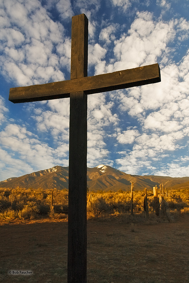 The black cross, title subject in a Georgia O'Keefe painting, stands in the afternoon shadow of the Taos Morada.