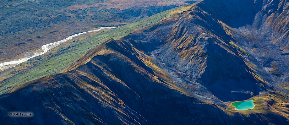 A braided river flows through the valley on one side of the mountains and a tarn lies within a valley on the opposite side of...
