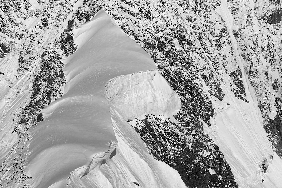 A cornice overlooks 14,000 feet of vertical rock and ice on the Wickersham Wall