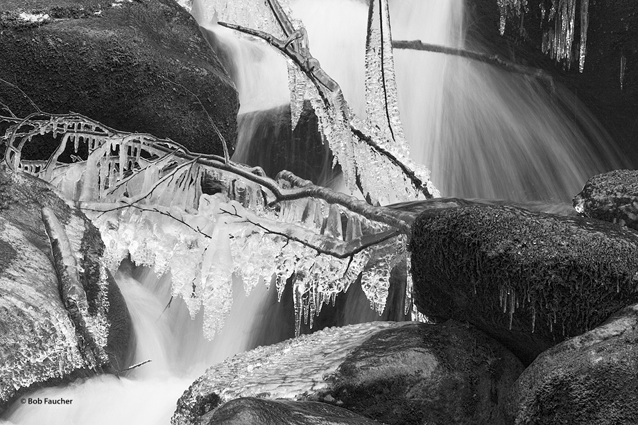 Icicles form on rocks and tree limbs over a flowing creek