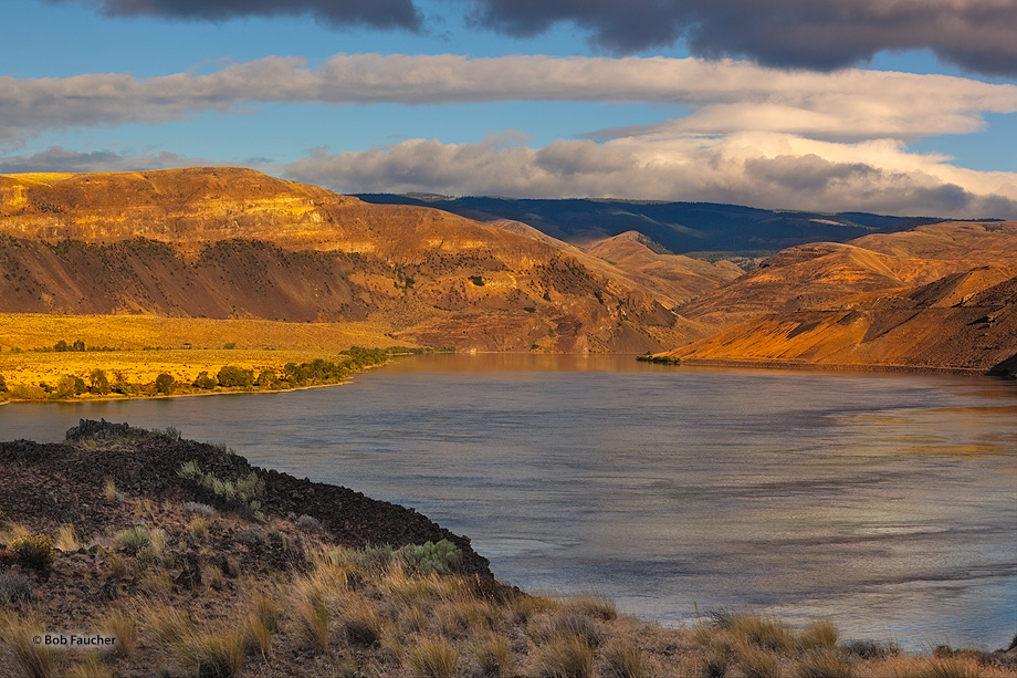 The Columbia River meanders through the upper Columbia Gorge, flanked by rocky hills, bathed in dawn's first light while storm...