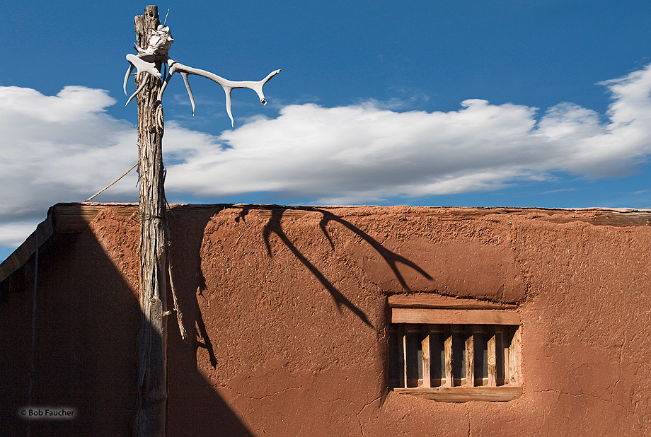 Shadow from mounted elk antlers encroach on an exterior window at El Rancho de Las Golondrios, a living history museum