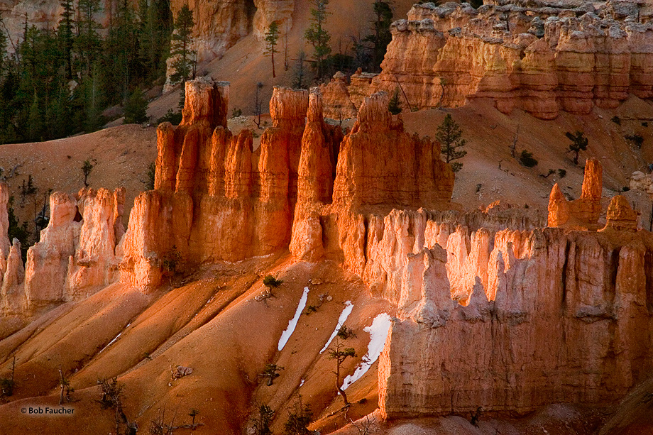 Early morning light makes the red hoodoos glow like fire while snow patches remain at their bases.