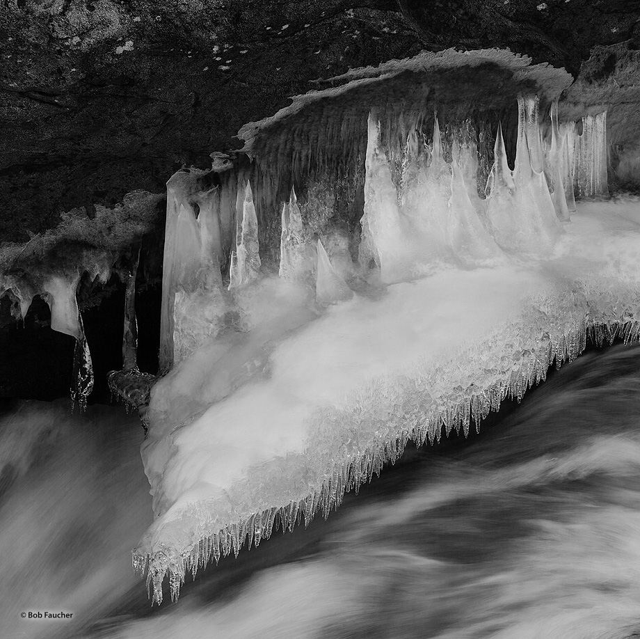 Snow covered ice shelf, formed on the upstream side of an overhanging rock in the Icicle River, has icicles hanging off the lower...