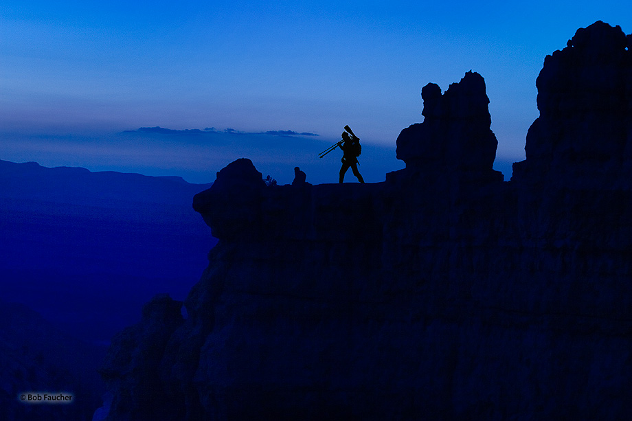 "A photographer positions himself on a ledge overlooking Bryce Canyon in the early ""Blue Hour"" of morning to be able to capture..."