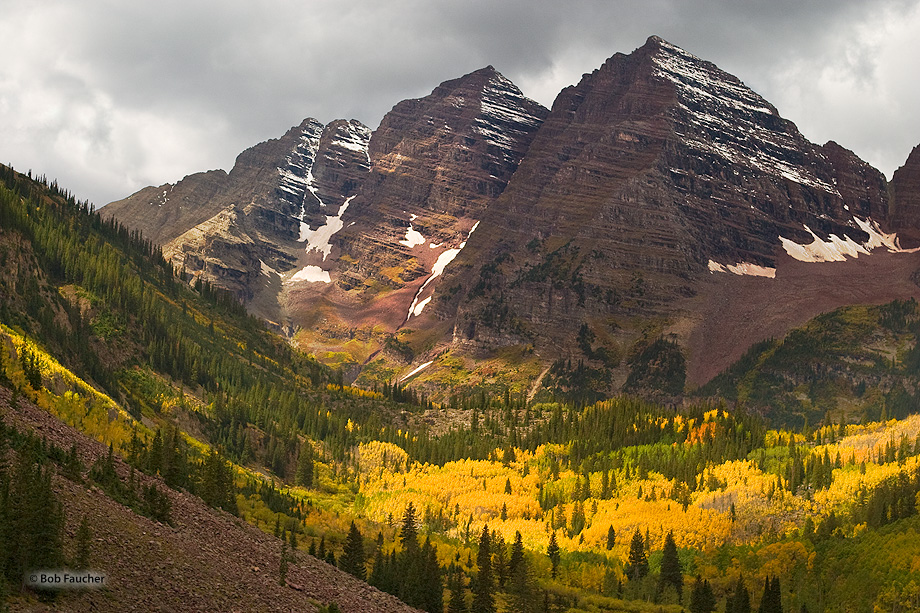 Storm clouds hang ominously over the peaks of the Maroon Bells. Yet a beam of sumlight manages to penetrate through the clouds...