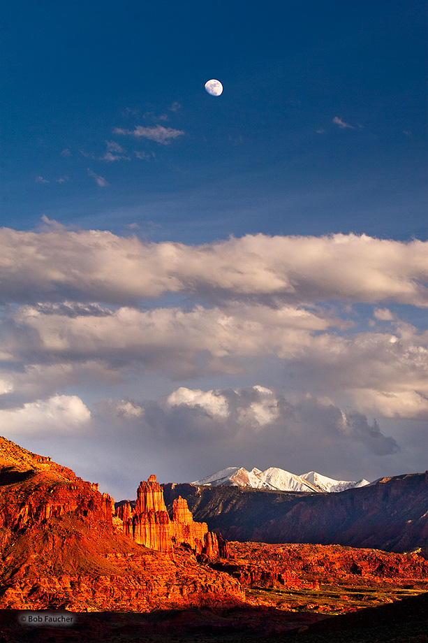 With the moon rising high above, Fisher Towers glow their signature deep red with strong sidelight in the afternoon.