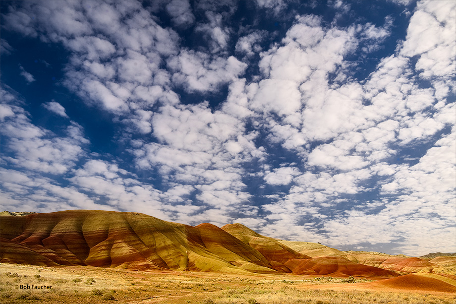 A glorious sky filled with popcorn clouds over the Painted Hills bathed by morning light.