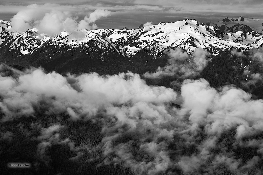 The Olympic mountains, with the valley shrouded in ground fog, catch the first rays of sunshine breaking under the cloud cover...
