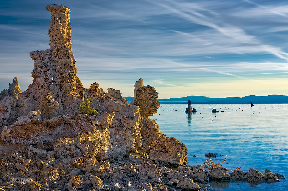 At sunrise a tufa tower is accenuated with direct, soft morning light while the sky and water reflect the warm light yielding...