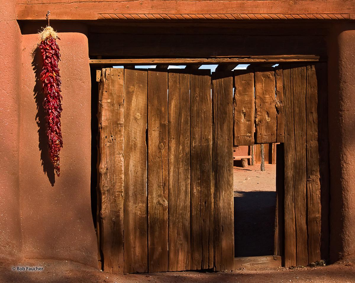 Ristras flank the main gate, with a pedestrian doorway (zaguan), into the walled central plaza of El Rancho de las Golondrinas...