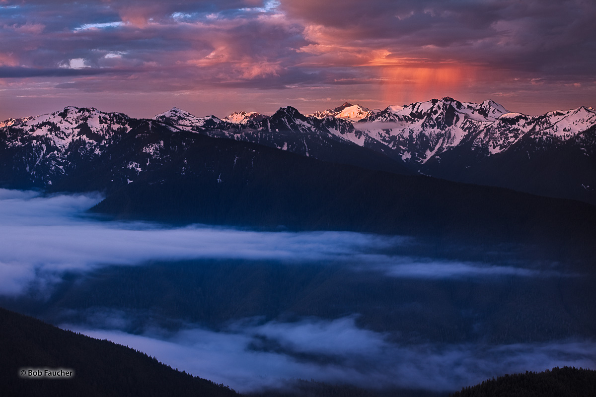 A squall forms over the Olympic mountains at dawn with first-light illuminating Mount Olympus as well as highlighting the clouds...