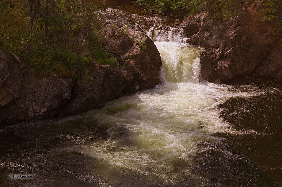 Rancheria River splits around a small rocky island forming falls on both sides