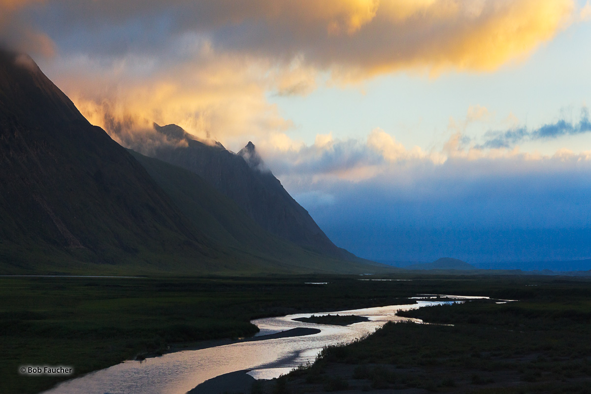 On an early morning, under low clouds illuminated by the rising sun, the Atigun River in Alaska's North Slope flows north from...