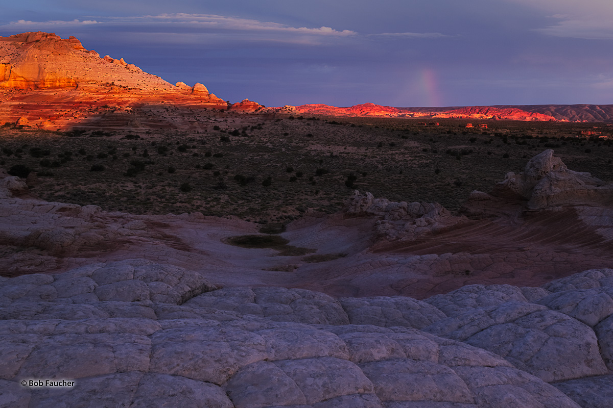 Beneath leaden skies stretching to Utah, the first direct rays of sunrise strike some of the taller formations at the White Pocket...
