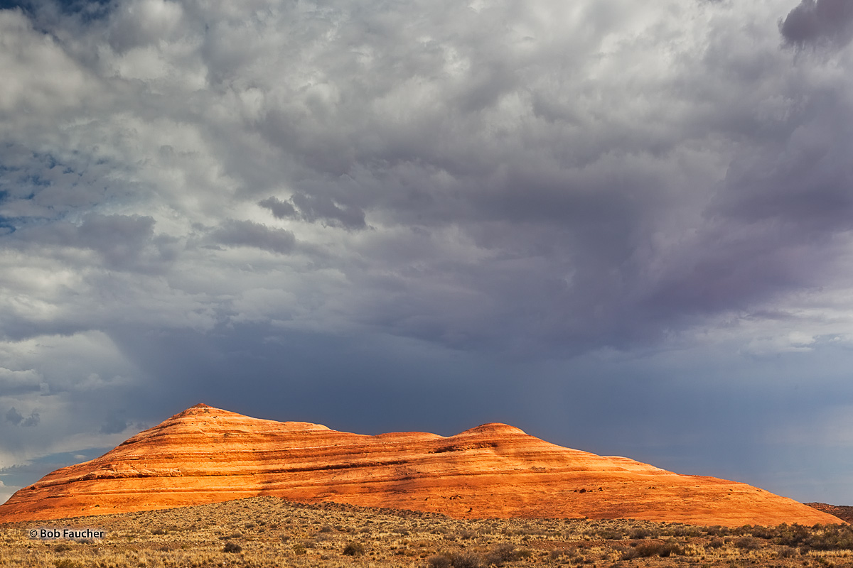 Beautifully stratified, erosion-rounded sandstone formation glows in morning light against dark foreboding skies in the Pedestal...