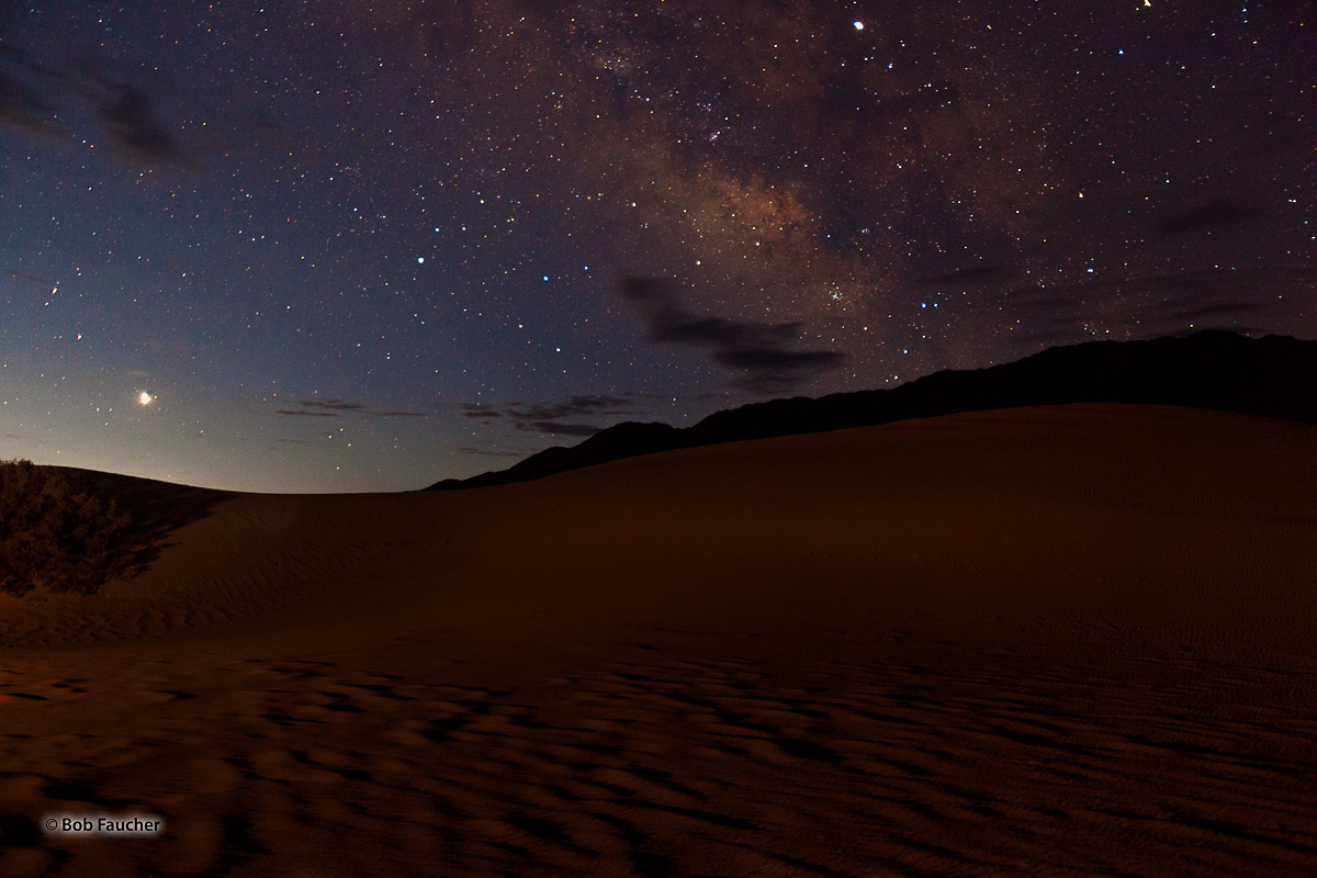 The Milky Way is poised over a section of the Mesquite Flat Sand Dunes. Artificial light with a red gel filter was painted onto...