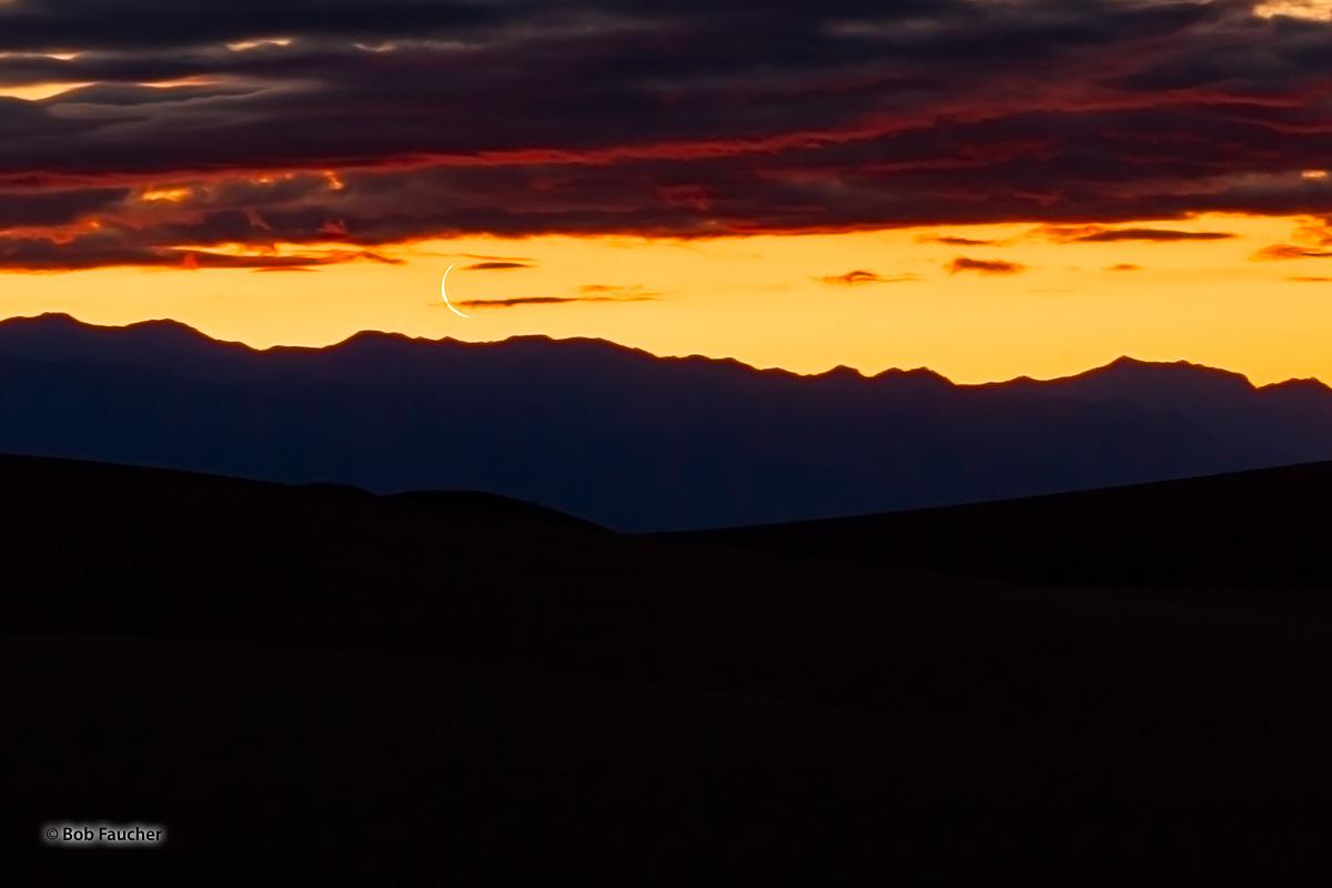 The waning crescent moon rises over the Amargosa Range during twilight.