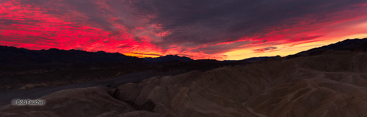 The rising sun turns the clouds a flaming red moments before it breaks over the crest of the Amargosa Range east of Zabriskie...