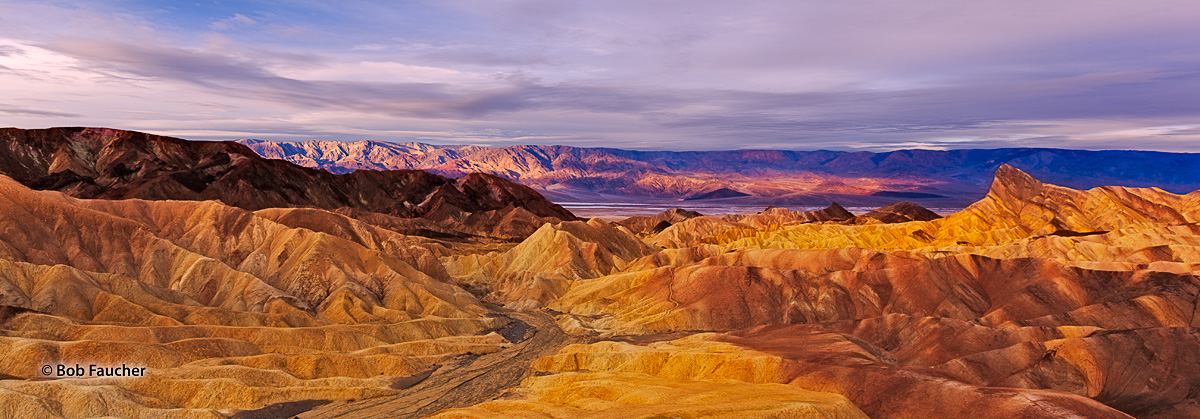 First light of morning strikes the Panamint Range across Death Valley from Zabriskie Point which is still in twilight. The colors...