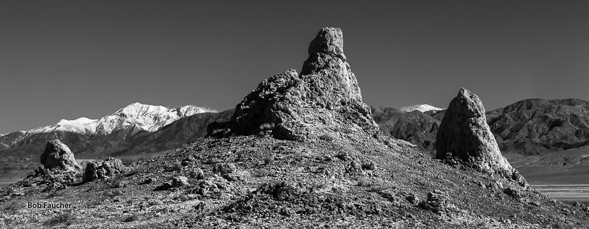 Snow covered lower Sierra peaks are framed by some tufa spires in Trona Pinnacles, a National Natural Landmark in the Searles...