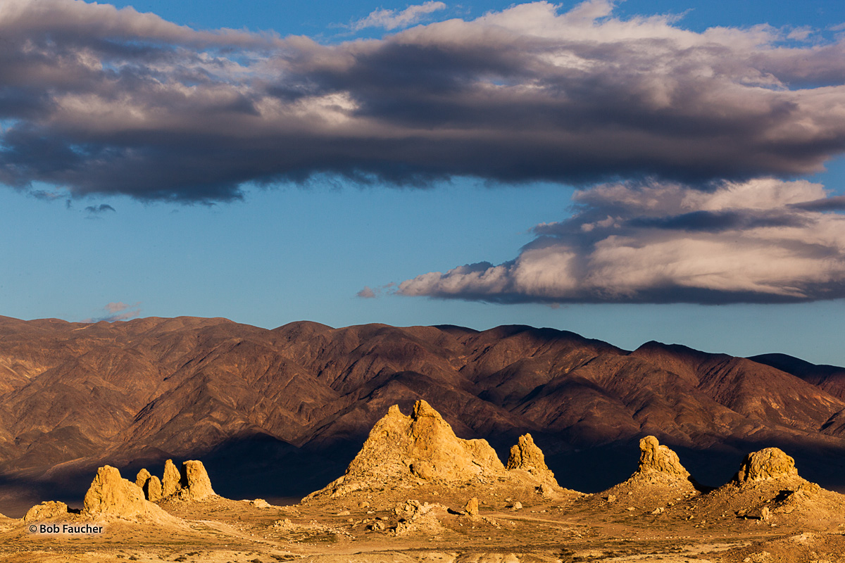Late evening light plays on some tufa spires, making them glow against the backdrop of brown hills in the Trona Pinnacles, a...
