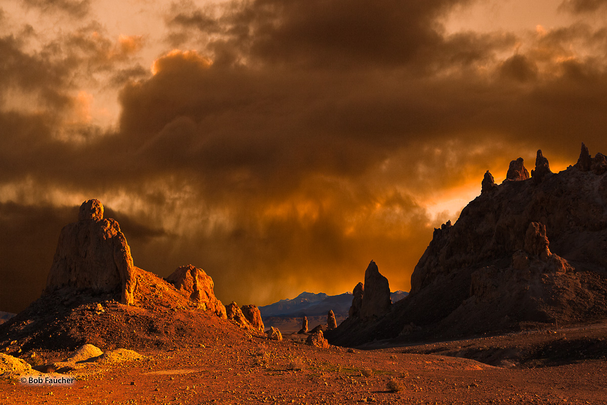 Morning direct light, breaking through dense but irregular clouds, catches a lineup of tufa spires in Trona Pinnacles, a National...