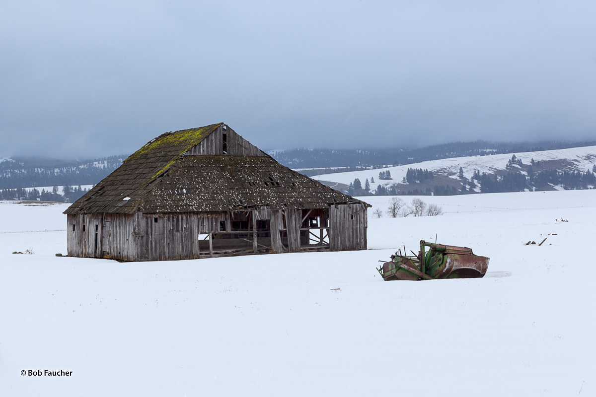 An old barn and farming implement remain stuck in the snow