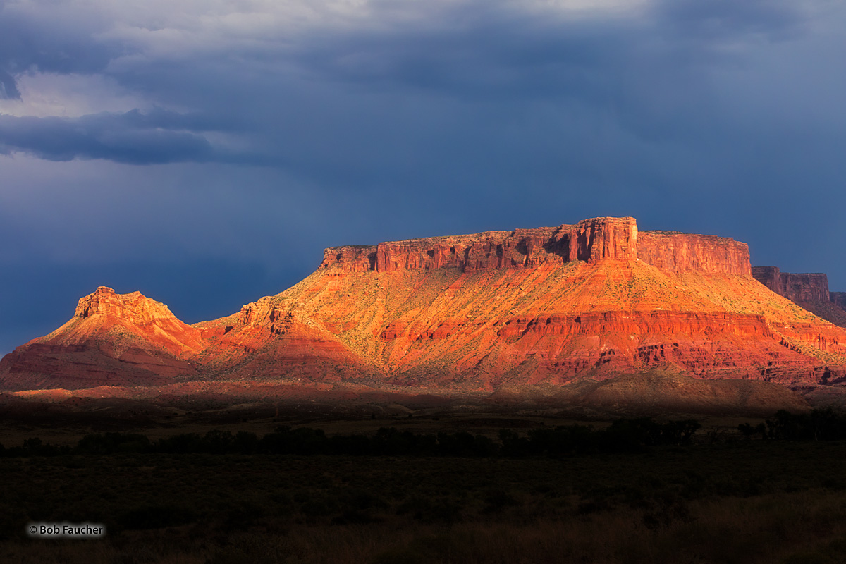 Under heavy cloud cover, late afternoon light streams across Professor Valley to wash Fisher Mesa, exaggerating the intensity...