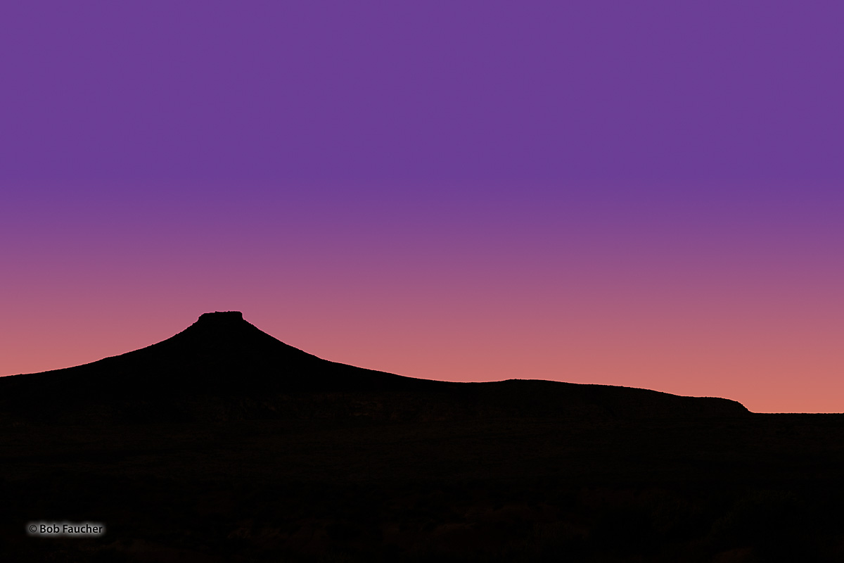 The brilliant colors of twilight behind the silhouete of an unnamed mesa across the expanse of Gould Wash near Hurricane, Utah...