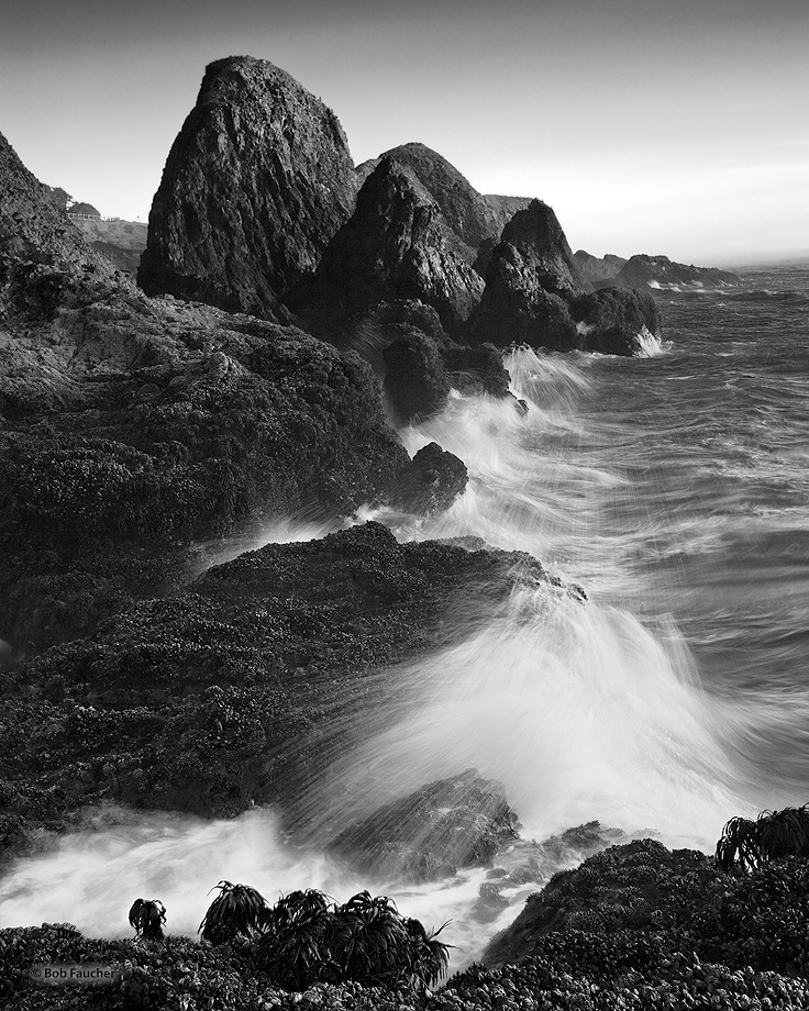 Swells from the incoming tide crash incessantly against the flanks of the rocks exposed to the ocean