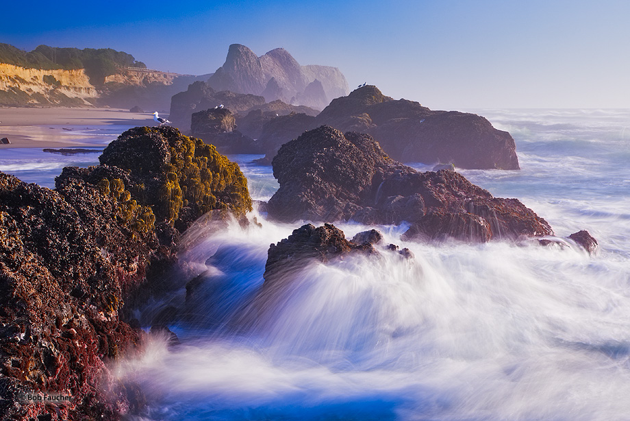 A long exposure creates long streaks of the splashing water as heavy surf crashes on the exposed rocks at Seal Rocks