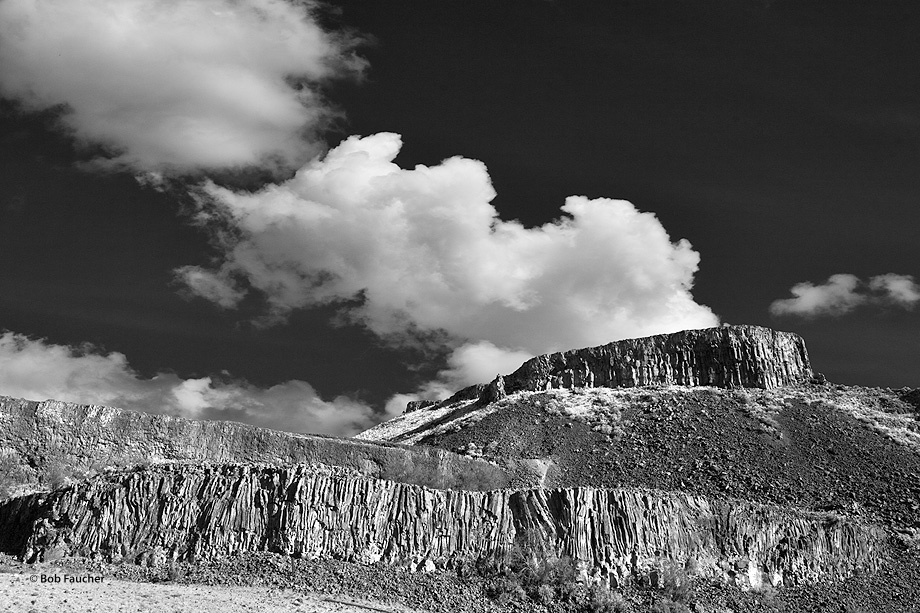 Late afternoon light strikes a basalt butte on the eastern side of the southwest-directed Moses Coulee as a cumulus cloud passes...