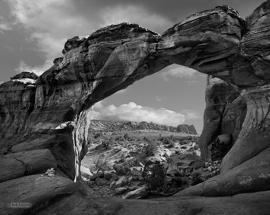 The sandstone fins of the Fiery Furnace are seen in the distance, approximately 1.2 miles away, as viewed through Broken Arch...